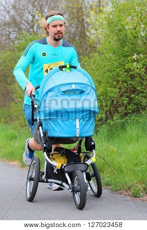 PILSEN CZECH REPUBLIC - APRIL 23, 2016: Happy young father running with pram on Plzensky pulmaraton (half marathon) run. Run for fun. Most popular international sport event in Western Bohemia.