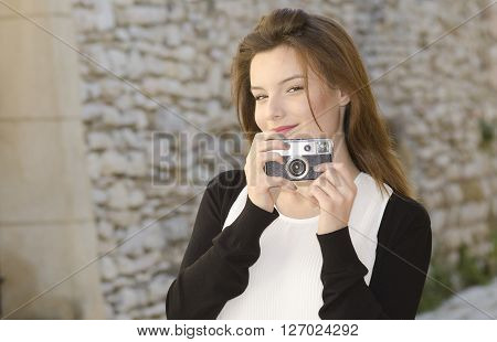 Pretty young girl holding an old camera and looking photographer