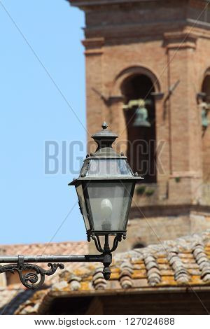 Some details of medieval Italian cities. Medieval street lamp with church tower in the background