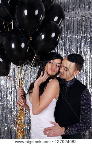 Wedding photo. Young couple with black balls on glittering background