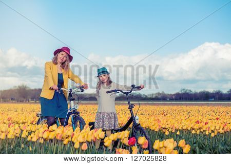 Smiling mother and daughter standing with their bicycles in a yellow tulips field at sunset.