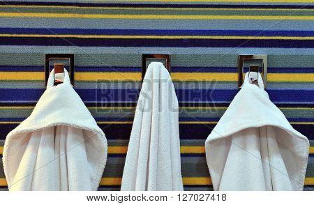 Three bathrobe and towel on the rack