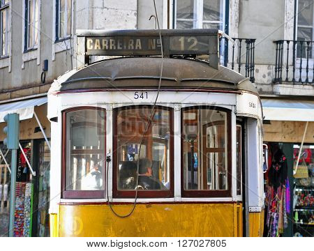 LISBON PORTUGAL - NOVEMBER 13: Yellow tram number 12 goes by the street of Lisbon city center on November 13 2013. Lisbon is a capital and must famous city of Portugal.