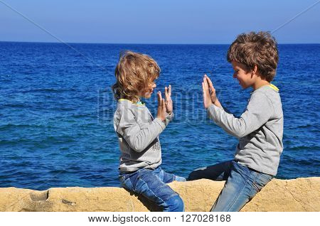 Two boys playing by the sea on summer