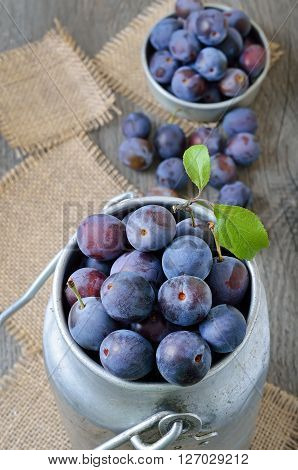 Fresh plums in bowl on the wooden table top view