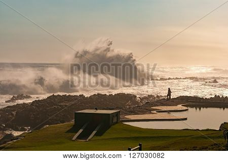 STORMS RIVER MOUTH SOUTH AFRICA - FEBRUARY 29 2016: Silhouette of unidentified tourists against the setting sun viewing the huge waves next to the swimming pool at Storms River Mouth