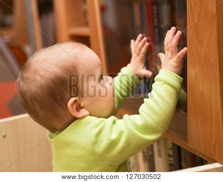 Baby or child wants to get a book from the bookcase