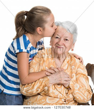 Granddaughter kissing her old grandmother on white background
