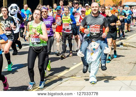 London United Kingdom - April 24 2016: London Marathon 2016. Runners in great costumes. Funny Baby holding an adult on its shoulders costume