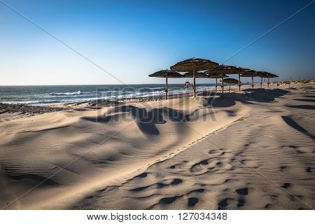West of the sun on the beach umbrellas in the background in Aveiro Portugal .