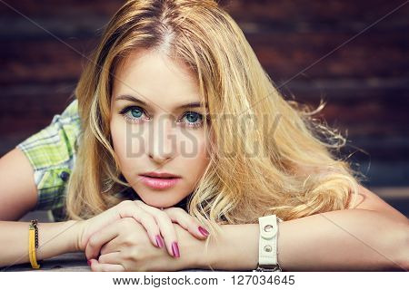Romantic Portrait of a Hipster Fashion Girl at Wooden Background. Toned Photo with Copy Space.