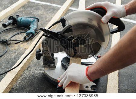 Worker cuts wood bars using a circular saw.