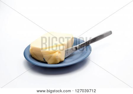 dish with butter from which a piece has been cut off with a kitchen knife