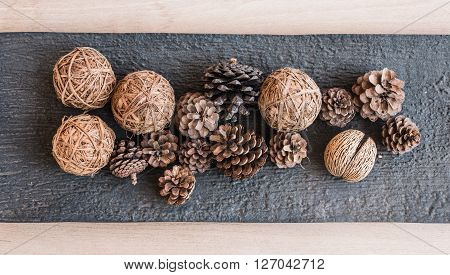asian natural group of pine cone pong pong seed and wooden rope ball put on stone tray and wooden background .