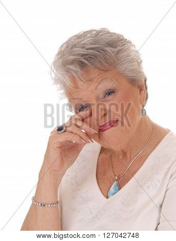 A lovely senior woman in her seventies holding her hand to her face and looking surprised isolated for white background.
