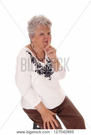 A pretty senior woman with short gray hair holding one finger over her mouth be quiet isolated for white background.