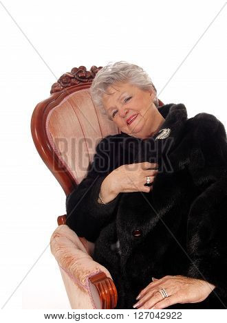 A lovely senior woman in a black fur coat sitting in a pink armchair smiling isolated for white background.