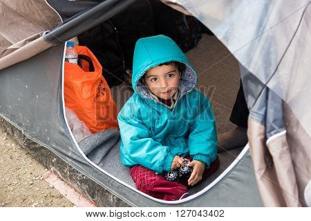 EIDOMENI, GREECE - MARCH 17, 2015: A boy plays in his tent on March 17, 2015 in the refugee camp of Eidomeni, Greece. For several weeks more than 10.000 refugees and immigrants wait here for the borders to open.