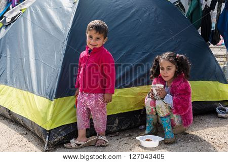 EIDOMENI, GREECE - MARCH 17, 2015: A boy and a girl sit by their tent on March 17, 2015 in the refugee camp of Eidomeni, Greece. For several weeks more than 10.000 refugees and immigrants wait here for the borders to open.
