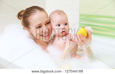 bathing in a bath with foam mother together baby son