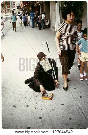 HONG KONG - CIRCA 1987: A blind beggar seeks alms on a sidewalk in Hong Kong.
