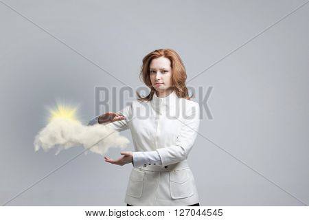 Young woman and sun shining out from behind the clouds, cloud computing  or weather concept