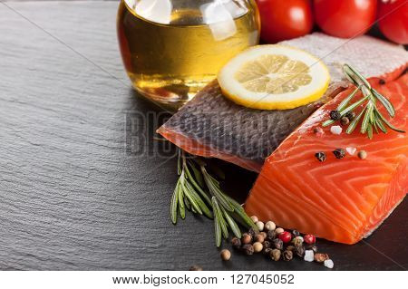 Raw salmon fillet, spices and vegetables on a dark  slate background
