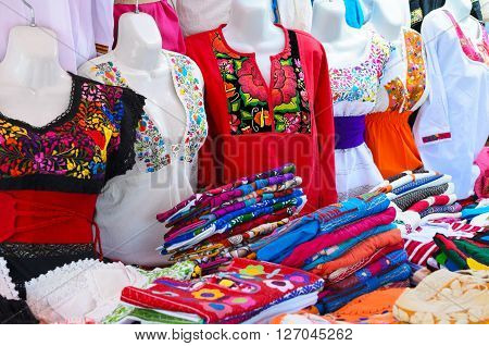 Colorful authentic Mexican women blouses on manikins at the market