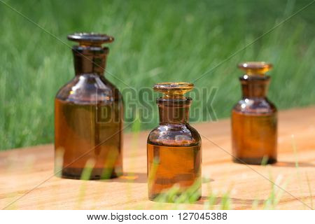little brown bottles on booden board and grass