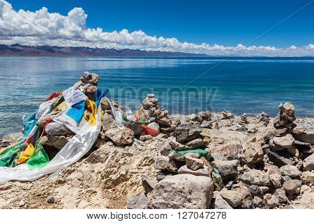 Marnyi stone with sutra streamers on the lakeside of Namtso Tibet China