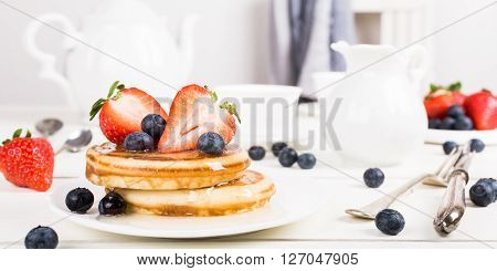 Healthy breakfast concept. Homemade pancakes with strawberries, blueberries and honey.