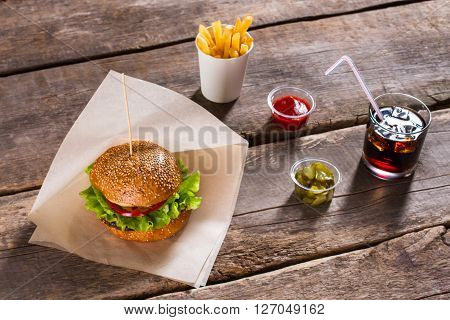 Burger and sliced pickles. Burger with cola and sauce. Small bowl of sliced pickles. Taste you will never forget.