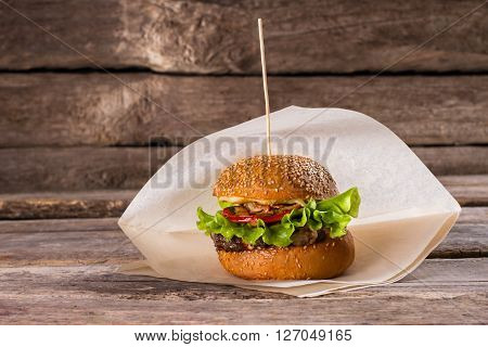 Fresh burger on a stick. Beefburger on wooden background. Juicy beef and fresh vegetables. Well-made burger in bistro.