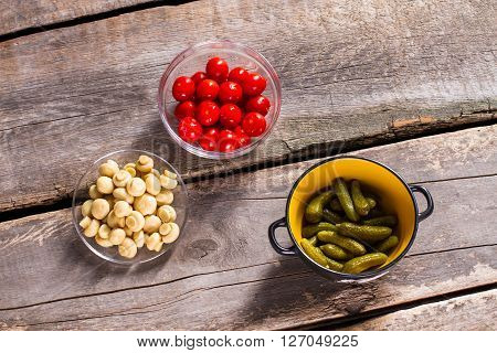 Tomatoes and mushrooms with pickles. Vegetables on brown wooden table. Homegrown vegetables that taste good. Ingredients for a dish.