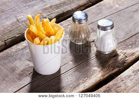 Fries with salt and pepper. Spices and fries on table. French fries at old bistro. Small snack at fair price.
