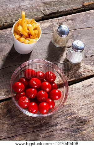 Tomatoes and fries with salt. Pepper and tomatoes on table. Processed food and fresh vegetables. Make your choice.