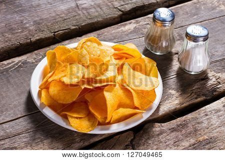 Chips with salt and pepper. Spices and chips on table. Chips from cafe's menu. Small portion of crispy snack.