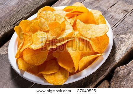Potato chips on a plate. Plate of chips on table. Chips served at retro diner. Simple junk food snack.