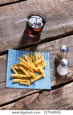 Fries on napkin and cola. Cola with fries on table. Crispy snack and sweet drink. Cholesterol and sugar.