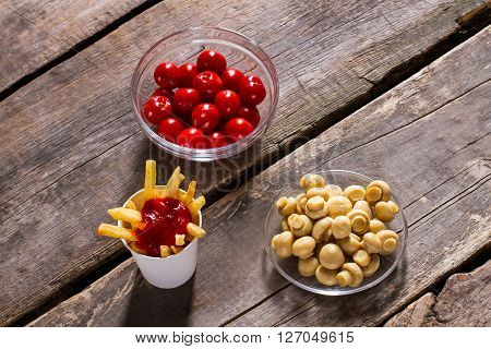 Fries with tomatoes and mushrooms. Champignons and tomatoes with fries. Wooden table with tasty food. Delicious high-calorie snack.
