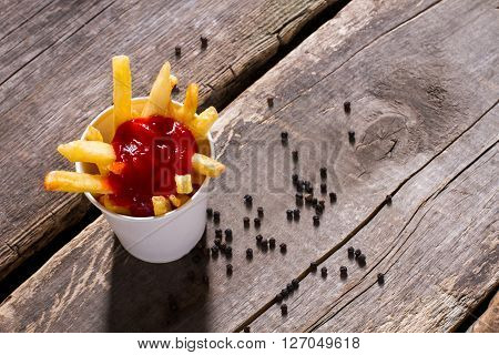 Fries with ketchup and pepper. French fries and whole pepper. Crispy fries on old table. Snack in fast food cafe.