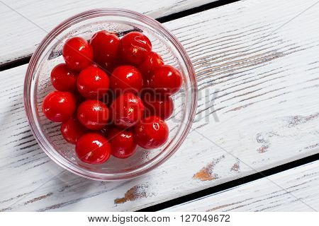 Red tomatoes in glass bowl. Bowl of small tomatoes. White table with fresh vegetables. Value your health.