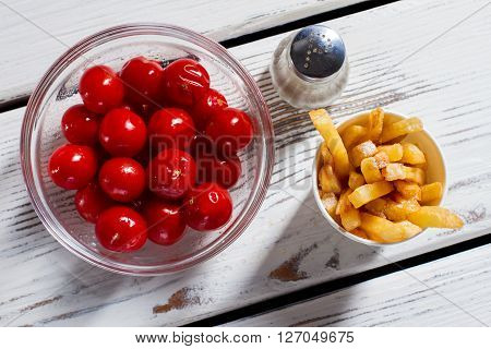 Tomatoes, fries and pepperbox. French fries with red tomatoes. Breakfast snack on white table. Vitamins and energy.