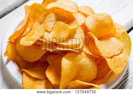 Potato chips on a plate. White plate with yellow chips. Fast snack at new diner. Good example of processed food.