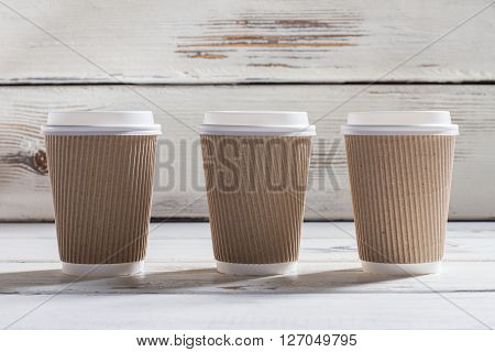 Ripple cups with lids. Three ripple paper cups. White wooden table with cups. Different grades of coffee.