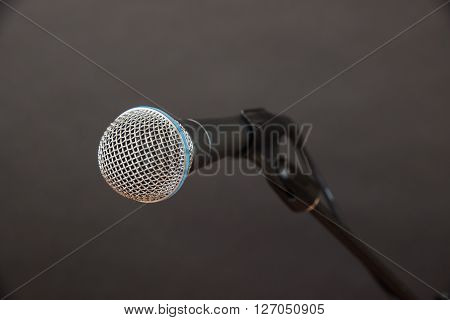 Clean shot of a dynamic microphone (mic) against a charcoal background at the perfect angle.
