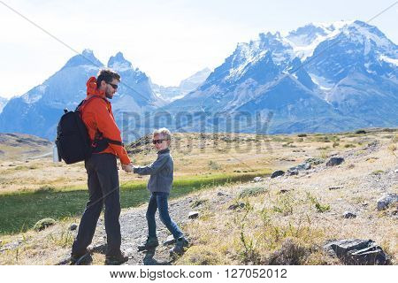 back view of playful family hiking in beautiful torres del paine national park patagonia chile active travel concept