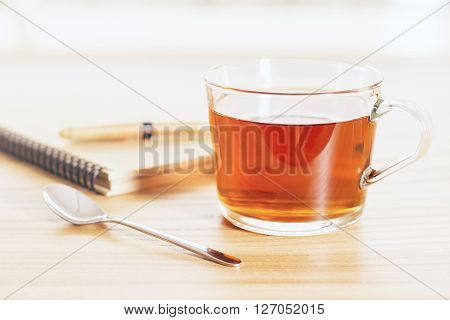 Cup of tea on wooden table with teaspoon and spiral copybook