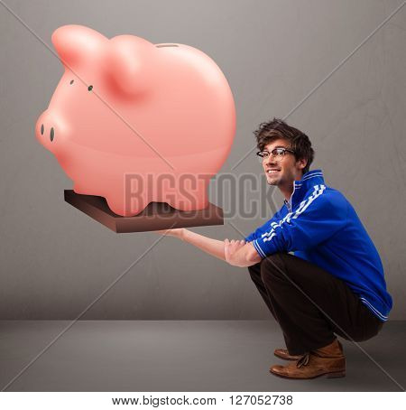 Handsome young man holding a huge savings piggy bank
