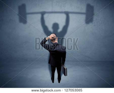 A confident young elegant salesman with briefcase facing a wall, looking at his strong, weight lifting shadow concept